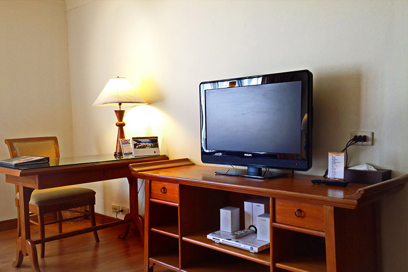 a desk and a television in a superior room